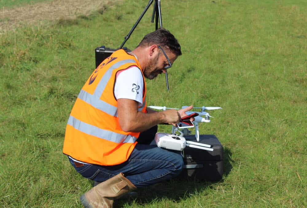 man in field sending images sent to customers of telecoms surveys